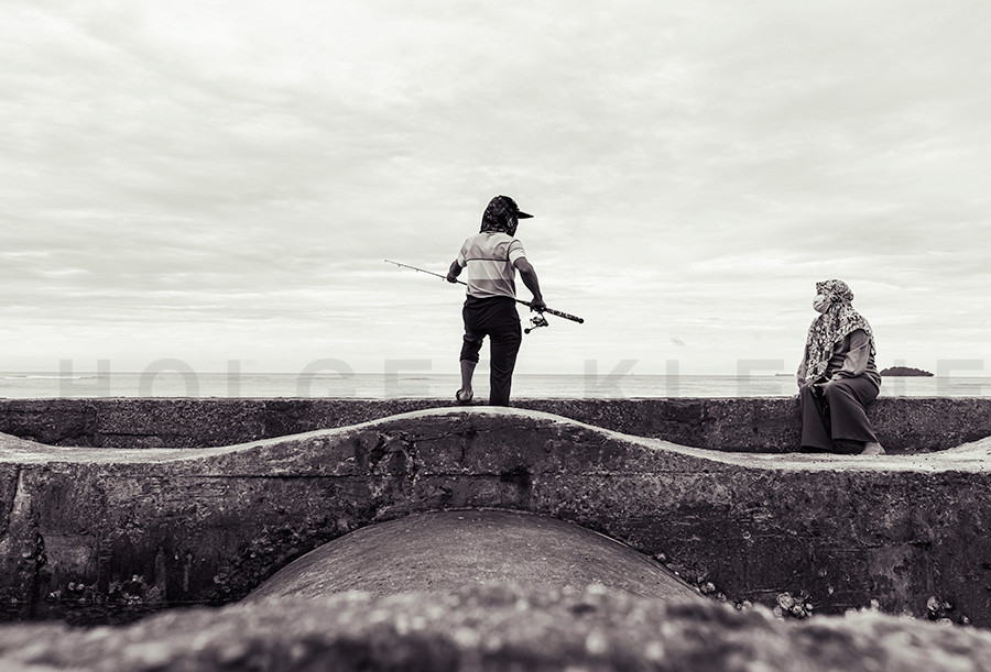 Young man fishing on a breakwater on the beach