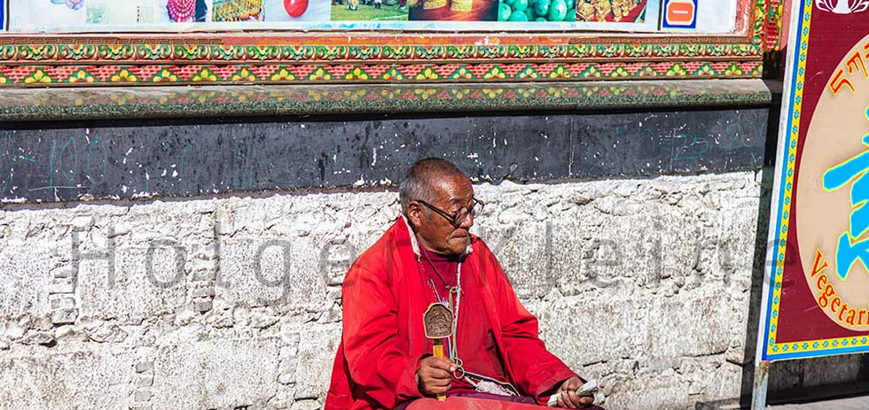 Old Tibetan man with crutches and Tibetan Prayer Wheel sitting on the road side