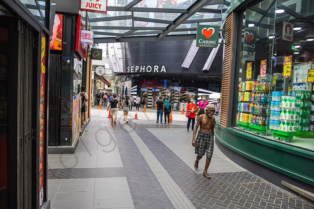 Homeless man walks through the shopping streets of Kuala Lumpur