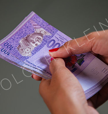 Female Hands with red nails counting 100 Ringgit banknotes