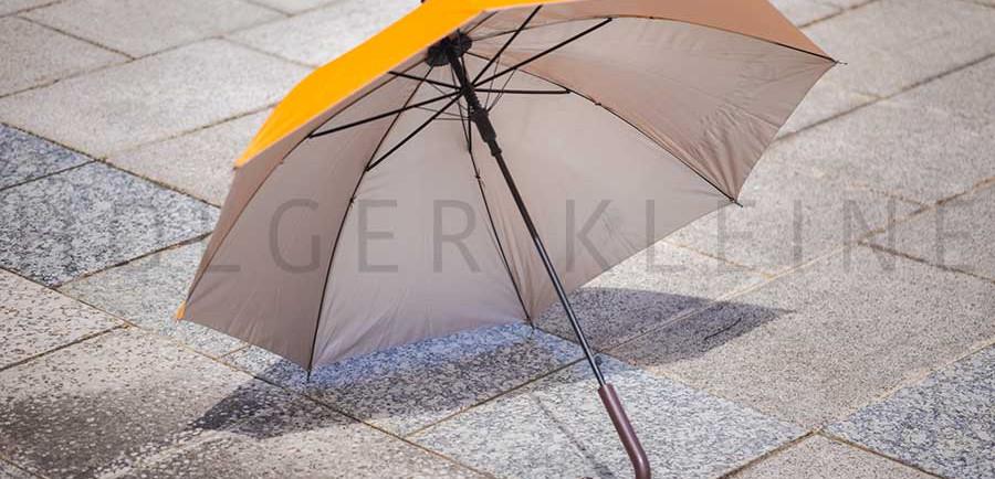 Orange umbrella on the street pavement.