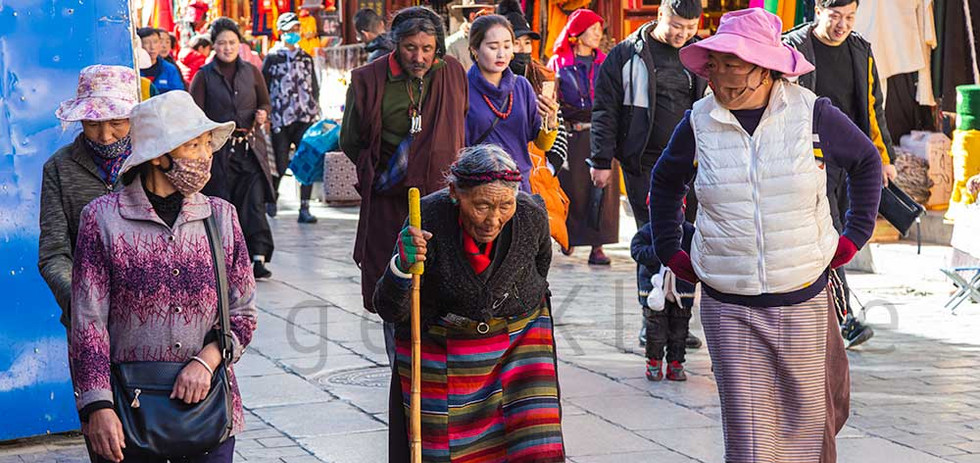 Old Tibetan woman in traditional Tibetan clothes and walking stick
