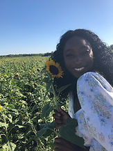 Tee-Tee smiling and holding a sunflower. Standing in a field of sunflowers