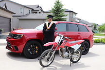 Daksh in a graduation gown smiling. Standing in front of a red SUV and behind a red dirt bike