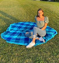 Carly in a print shirt and jeans. Sitting on a blue plaid picnic blanket on bright green grass.