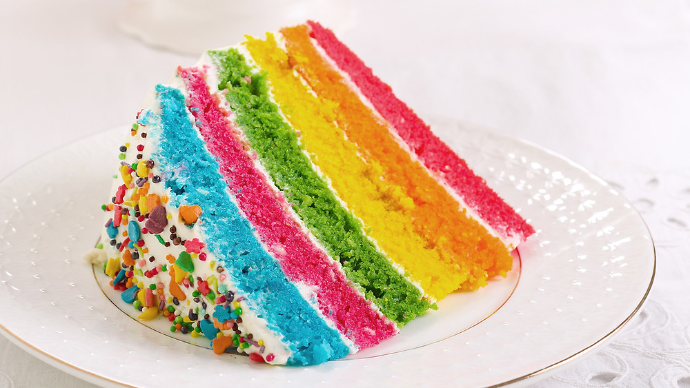 slice of rainbow coloured cake suggesting how do I stop talking so fast