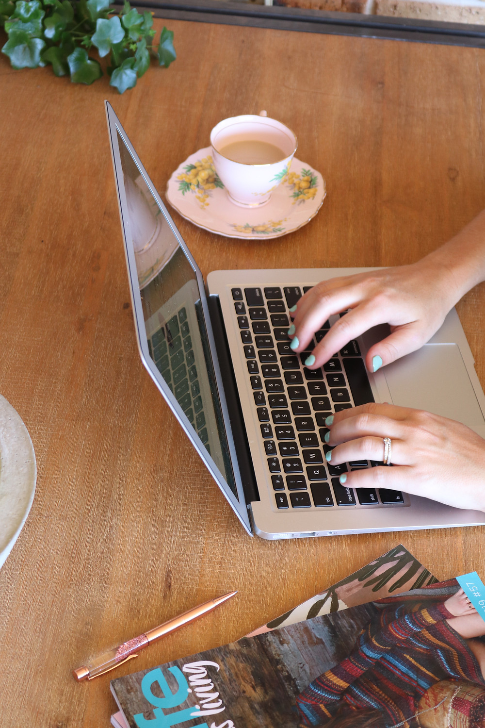 Lady typing on laptop with cup of tea beside her