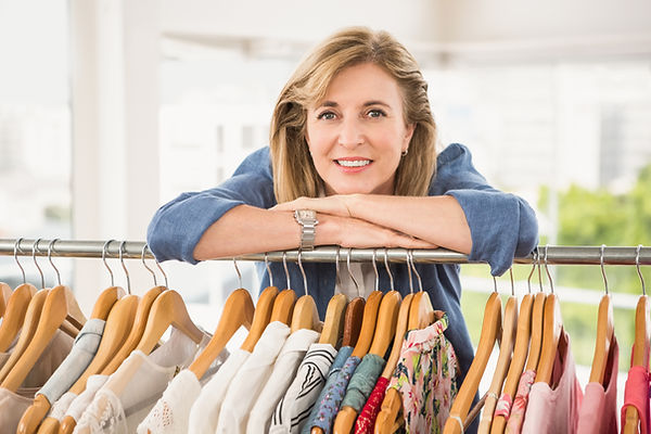 portrait-of-smiling-woman-leaning-on-clothes-rail--P5UVZJW.jpeg