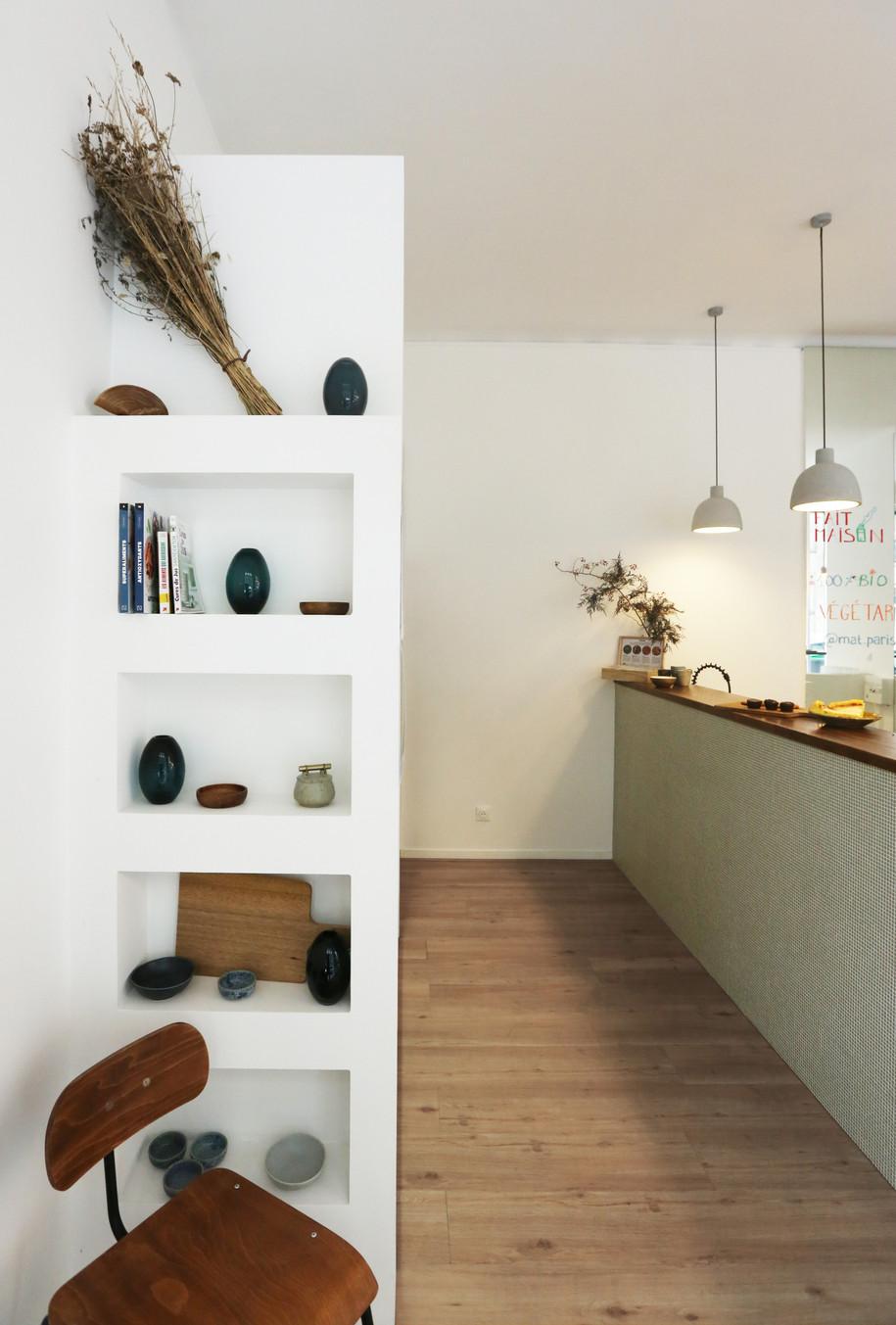 Réhabilitation complète d'un local. Création d'un univers accueillant grâce à une harmonie de matériaux. Mini-mosaïque et bois huilé s'équilibrent et s'accordent au sein d'un univers adapté à la demande des propriétaires : des amoureux d'une cuisine saine et végétale.