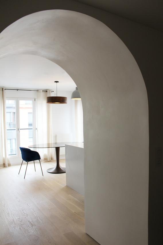 Aménagement d'un appartement neuf.  Ici, la valorisation de l'espace a été faite grâce à la réalisation d'un grand mur en tadelakt blanc.  Apprécié comme une zone de rangement, mais aussi guide de circulation, il apporte à cet espace une tendance contemporaine et épurée.