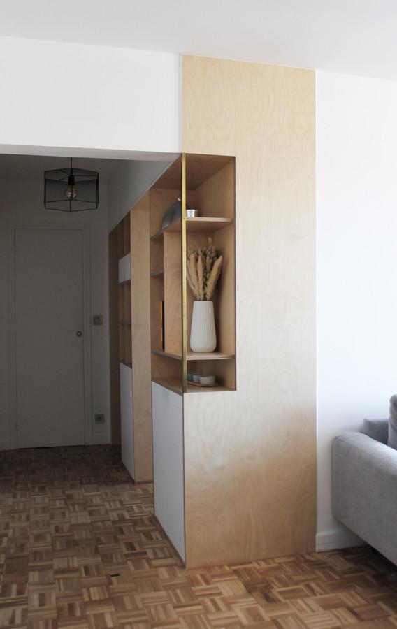 Imaginé comme le centre de l'appartement, la création de ce grand meuble a été pensé comme un véritable mur.  Traversant chaque espace grâce à des portes coulissantes camouflées, ce dernier reste visible depuis toutes les pièces. Ses matériaux bruts et naturels l'intègrent facilement au reste de l'appartement .