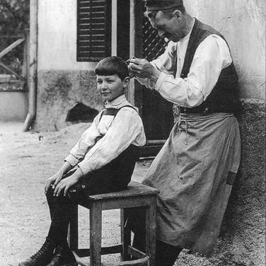 """Schuldiener beim Haareschneiden, Schulgasse, 1903, aus F. X. Mannert """"Ischl im Wandel der Zeit 2.0"""""""