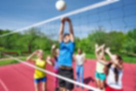 Crianças que jogam o voleibol