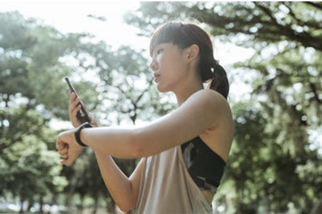 standing girl checking connected device to his selfphone