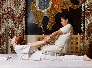 Young-female-receiving-massage-by-therap