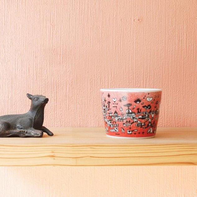CHOCO ARITAの蕎麦猪口(そばちょこ)を制作させて頂きました。 -----------------------------------CHOCO ARITAは肥前地区で焼かれたのが最初とも言われる「蕎麦猪口」のブランドです。 「有田で作られた器」ですが「俗に言う伝統的な染付や赤絵付の有田焼」ではありません。(有田焼と言っても間違いではないのですが…) 器を何焼どこ焼ではなく、ファッションにおけるTシャツを好きな絵柄やイラストレーター、 アーティストのものを買うような感覚で買える器もあってもいいのかなと考えました。 また、蕎麦猪口の新たな使い方をみんなで考えてもらい、実際に使ってもらえるといいなという提案でもあります。 47都道府県在住のイラストレーターさんに各1人以上、全50柄を目指しています。