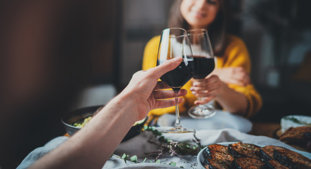 Cropped image of romantic couple making cheers with glasses of red wine during date in res