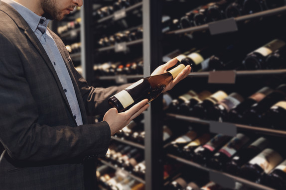 Sommelier man with wine bottle near rack store restaurant with exquisite drinks.jpeg