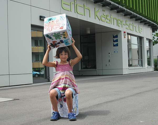 Emma sitzt auf einem selbst ausgemalten MAKI-Sitzwürfel vor der Erich Kästner-Schule
