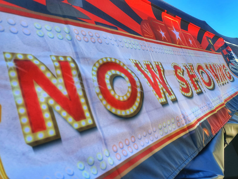 Banner with the words Now Showing in red, with an outline of lights on each letter.
