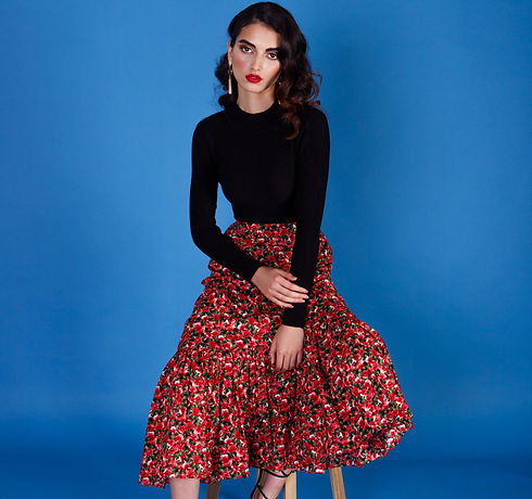 Model sitting on chair dressed in our floral printed red skirt.