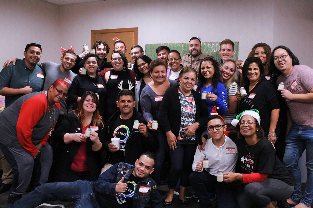 Community Cocina workshop attendees posing for a group photo with bottles of coquito in hand.