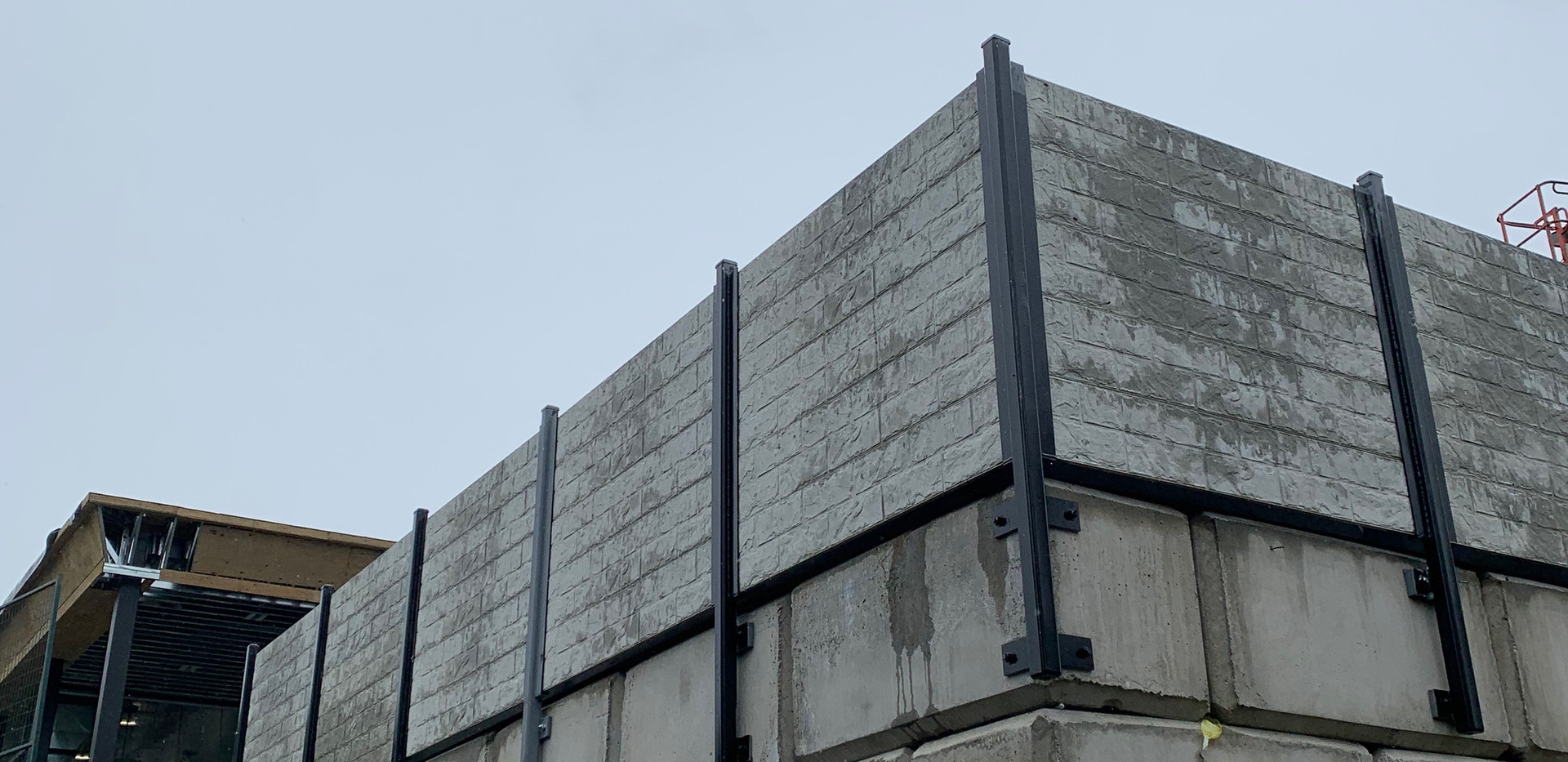 Concrete fence on retaining wall