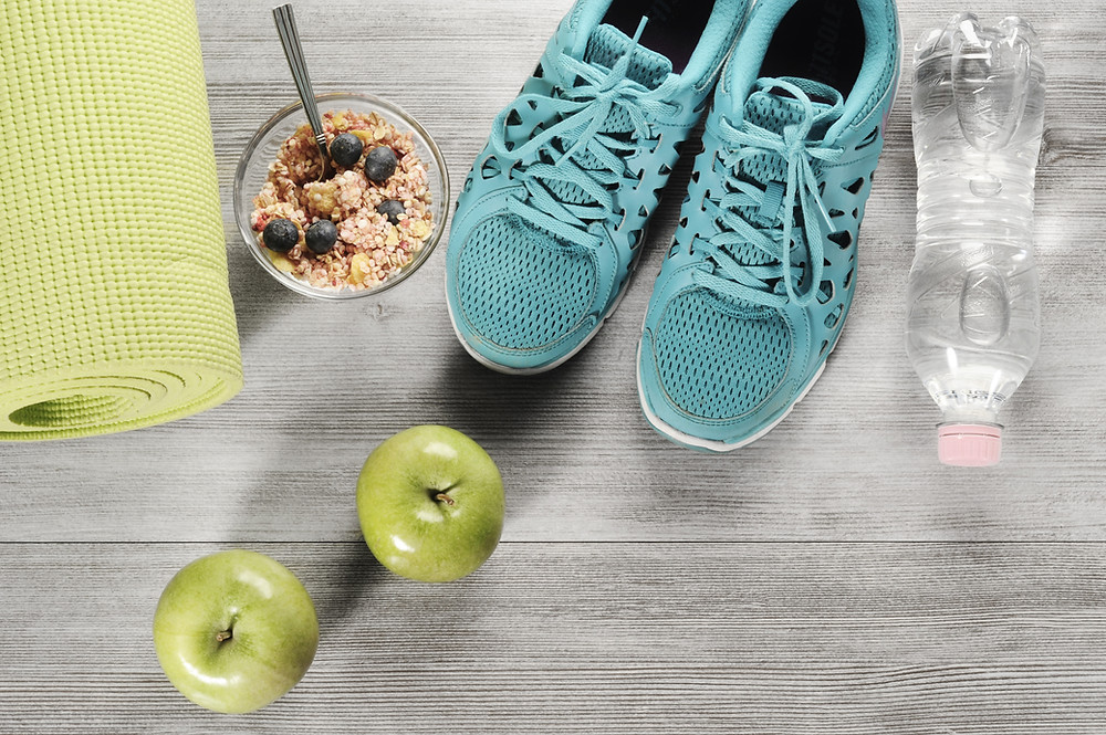 Image of healthy breakfast, hydration in form of a bottle, yoga mat and running shoes to reflect healthy balanced living.