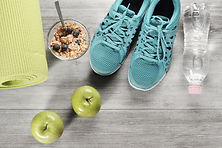 a yoga mat, granola, apples, sneakers, and water