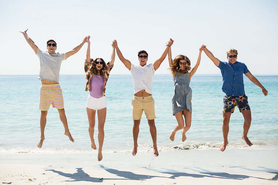friends-jumping-with-arms-raised-at-beac