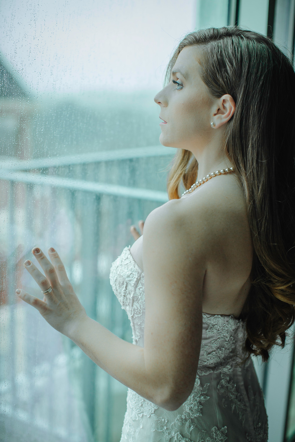 A woman in a bridal gown with pearls around her neck looks out a window with her hands pressed against the glass.