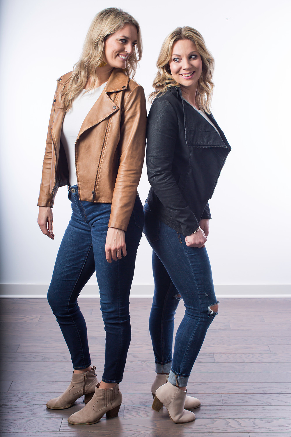 Two women standing back to back and looking toward each other.  One woman is wearing a brown leather jacket and jeans.  The other woman is wearing a black leather jacket and distressed jeans.