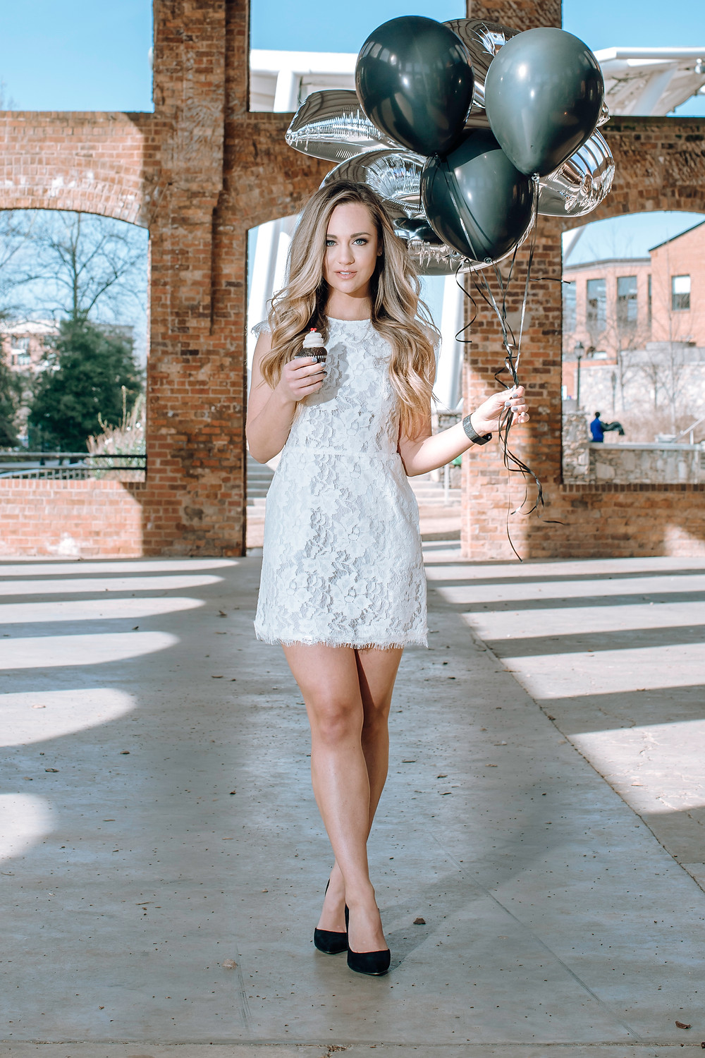 A woman in a lace white dress is standing crossed leg whilst holding a cupcake in one hand and balloons in the other hand.