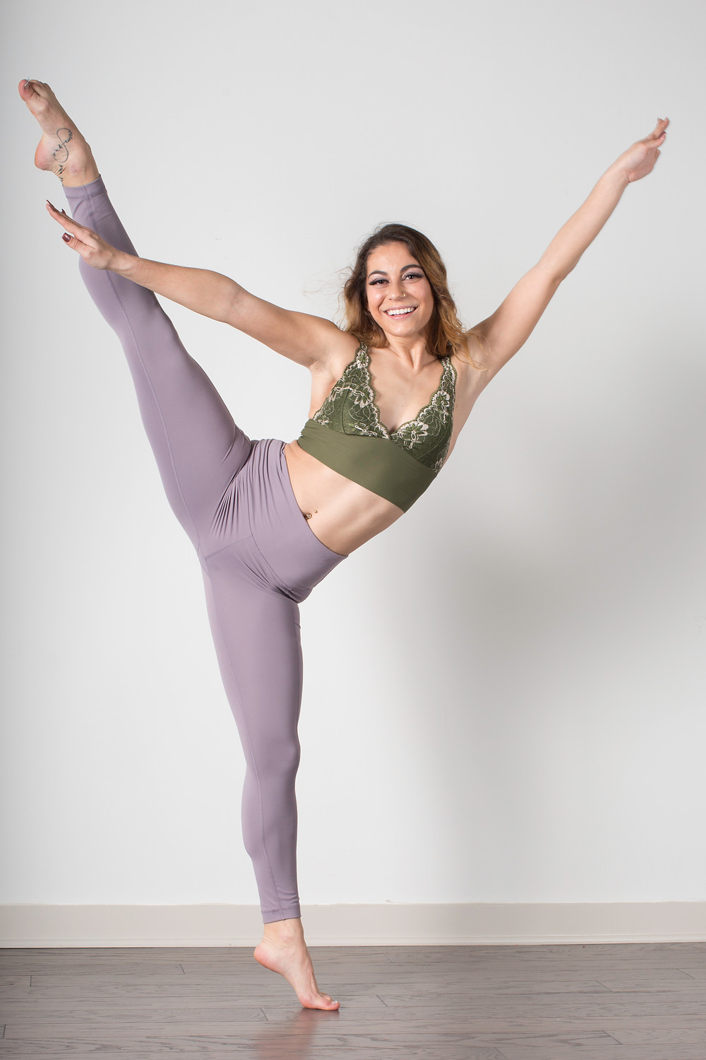 """A woman is in front of a white wall wearing a green sports bra and light purple yoga pants.  She is on one foot and the other leg is kicked nearly vertically and her hands up in a wide """"V"""" as she faces forward toward the camera."""
