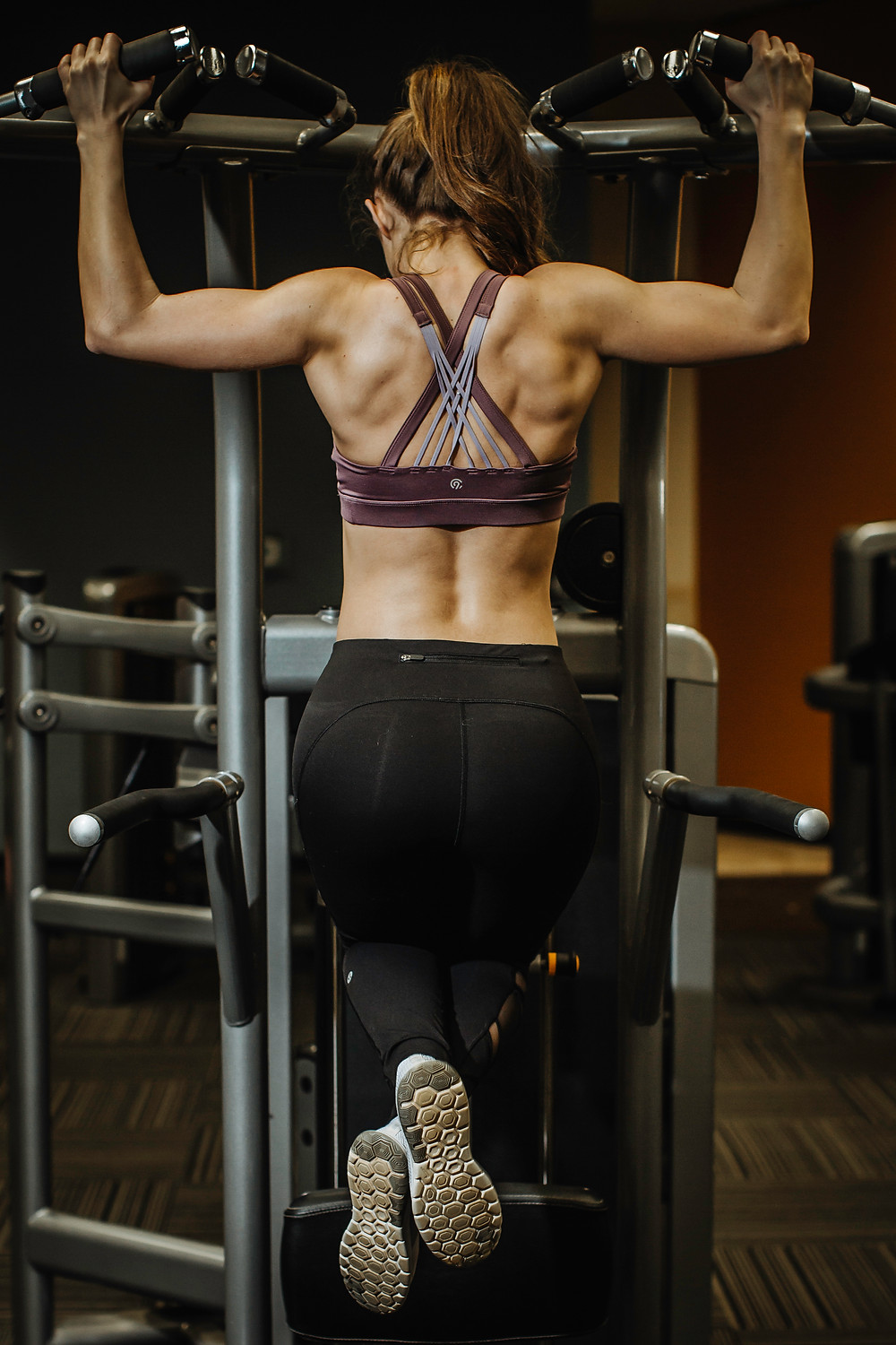A woman wearing a sports bra and yoga pants is pulling up on an exercise machine with both hands.