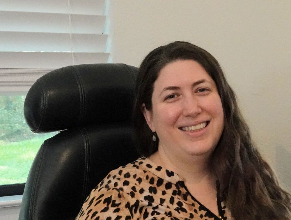 Speech language pathologist Tallulah Breslin smiling in her computer chair