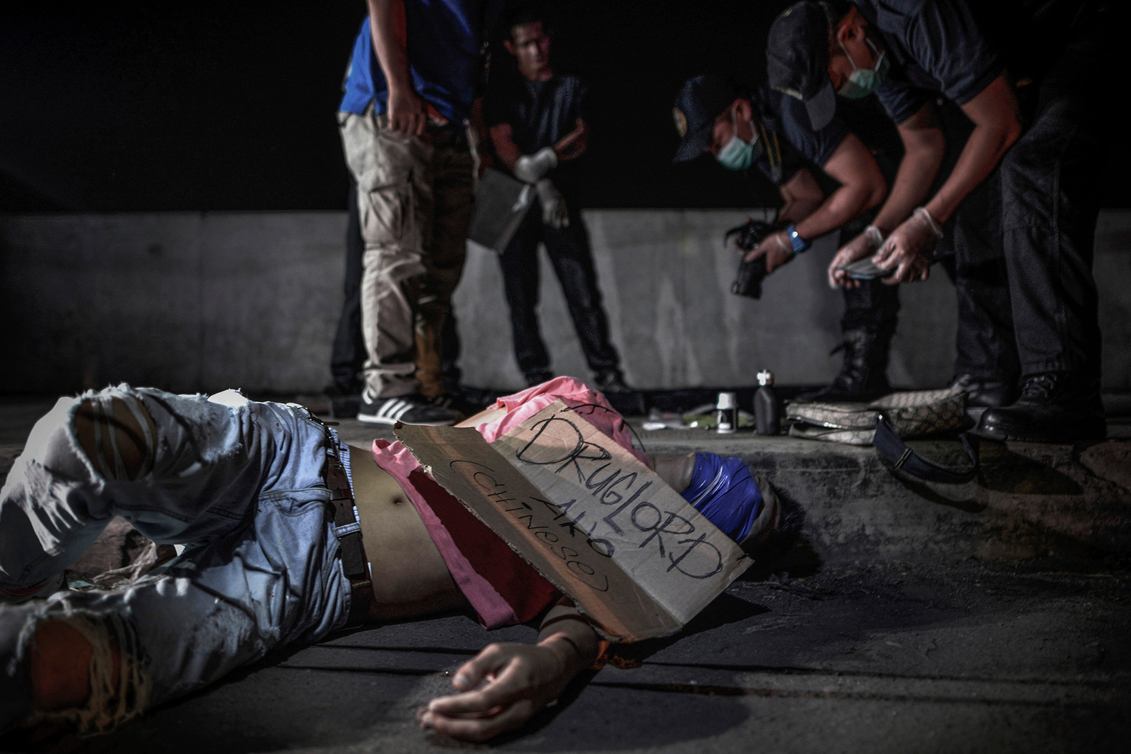 """The body of a man and victim of a vigilante-style execution with his head wrapped in tape lies on a street in Manila, Philippines, July 28, 2016. A sign placed on next to the body reads """"I am a Chinese drug lord."""""""