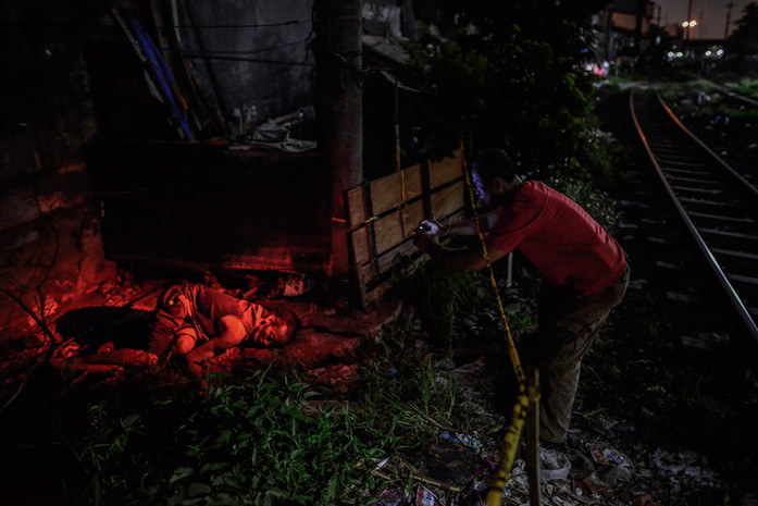 The body of a suspected drug pusher lies dead next to railroad tracks following what police say was a drug buy-bust operation in Manila, Philippines, July 18, 2016. The man had allegedly fought back against undercover cops who came to buy drugs from him.