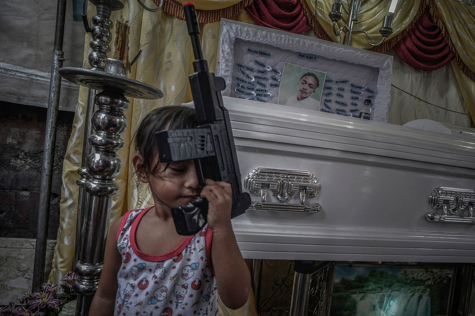 "Bea, sister of 17-year-old Harold Bulan, holds a toy gun next to his coffin during his funeral wake in Quezon city, Philippines, December 7, 2017. Harold was last seen with his cousin Jerico Garcia and their friend Jomari Siñerez around midnight of November 22, 2017. Hours later, their bodies were dumped in different parts of town. Their throats had been sliced. A cardboard attached next to one of them listed the names of their friends. ""You are next!"" the writing on the sign read."