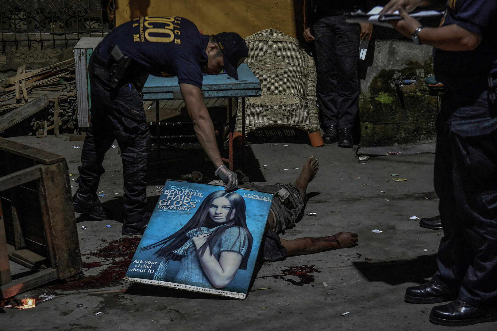 A police investigator covers a shooting victim with a cardboard poster in Quezon city, Metro Manila, Philippines, February 9, 2017.