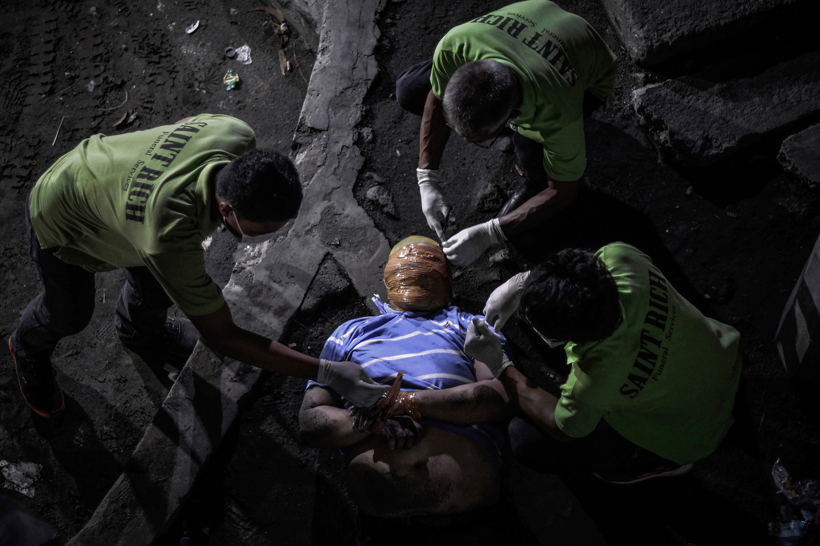 Funeral workers remove the tape wrapped around the head and wrists of a man who police say is a victim of a drug related vigilante execution in Manila, Philippines, September 21, 2016.