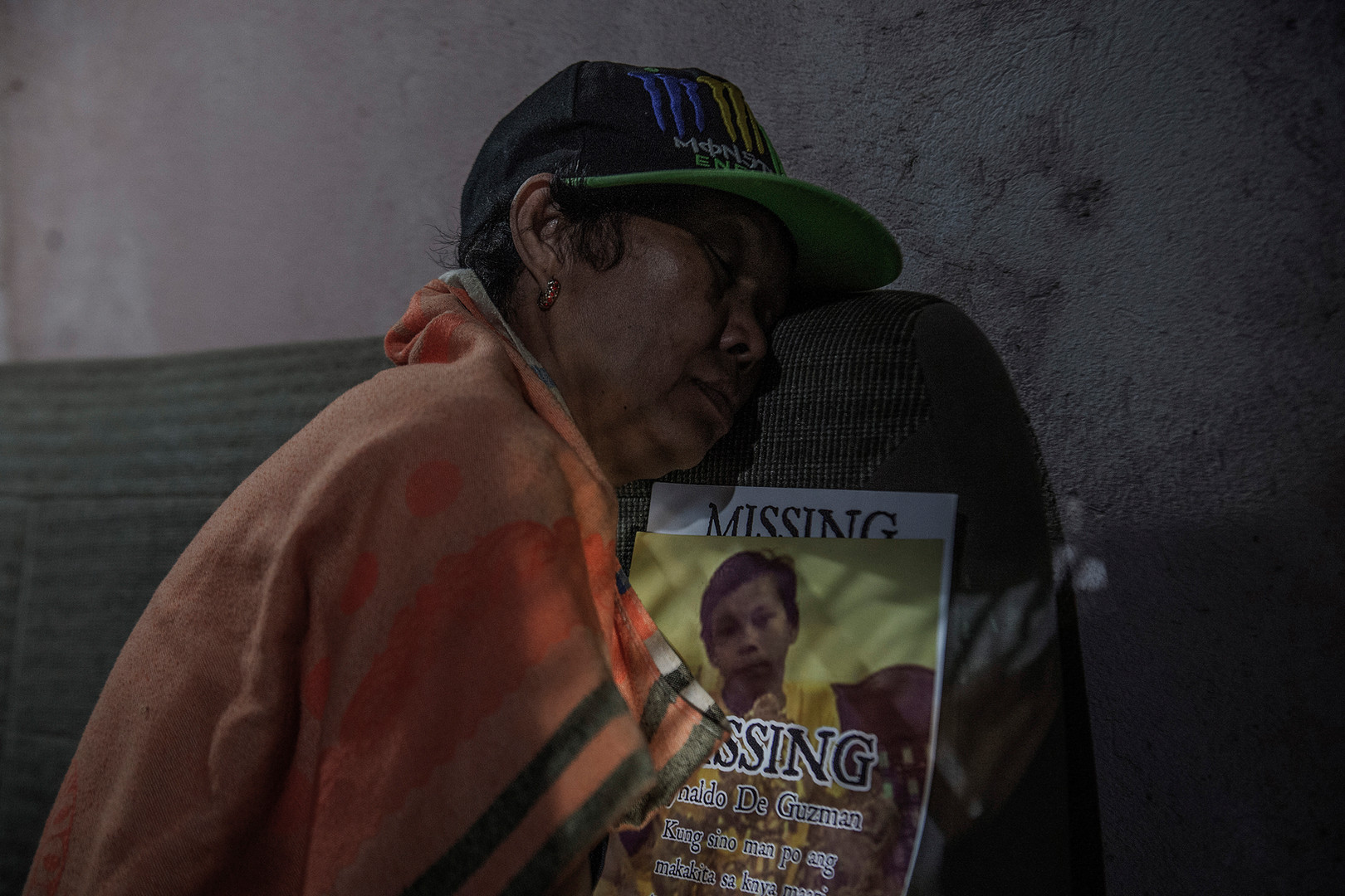 """Lina De Guzman holds a missing sign for his 14-year-old son Reynaldo """"Kulot"""" De Guzman. Kulot was last seen with his neighbor Carl Angelo Arnaiz on August 18, 2017 in Cainta, Rizal. Hours after they went missing, Carl allegedly robbed a taxi and figured in a shootout with police officers ten kilometers away in Caloocan. Police say packets of shabu and marijuana were recovered from Arnaiz. Kulot remained missing until 20 days later when his body was found some 100 kilometers away floating in a creek in Gapan, Nueva Ecija. His body bore 30 stab wounds and his head was wrapped in tape."""
