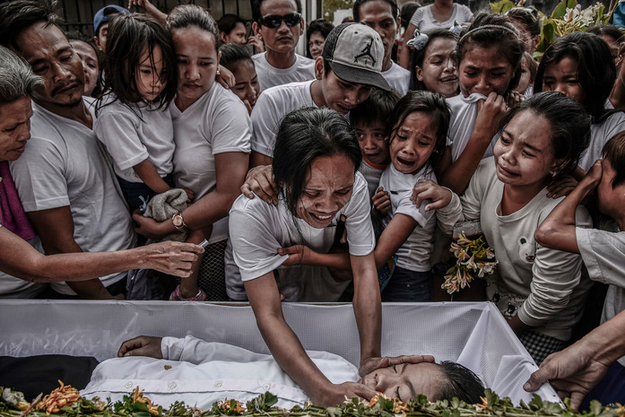 Family and friends of 13-year-old Aldrin Pineda weep during his funeral in Manila, March 14, 2018. Aldrin was playing with his friends in their neighborhood when Omar Molinao, a police officer, shot him dead. Officer Malinao claims he was on patrol in the area when he tripped and accidentally fired his gun.