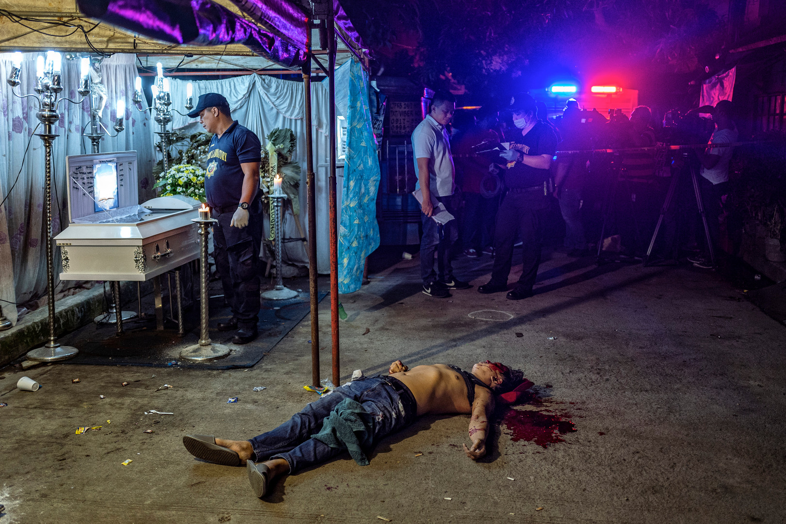 The body of Michael Nadayao lies dead on the street next to a funeral wake, after he was shot dead by unidentified men  in front of mourners, in Quezon city, Metro Manila, August 31, 2018.