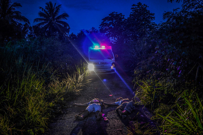 "Bodies of two men dumped in an isolated stretch of road are seen in Quezon city, Metro Manila, Philippines, June 22, 2017. Signs placed over their bodies both read ""I am a thief, do not tolerate me."""