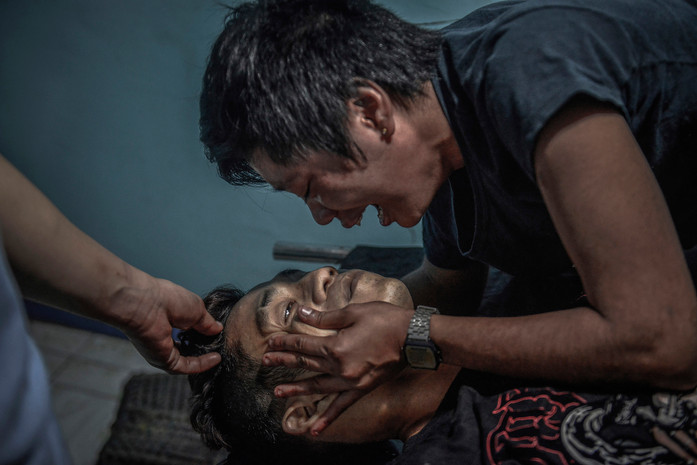 Ginnalyn Soriano weeps over the body of her elder brother Julius, who allegedly fought back and was killed by police during what they said was a drug sting operation, at a morgue in Malabon, Metro Manila, Philippines, June 22, 2017. At the morgue, the family noticed Julius' wrists had cuff marks. The arm had a bullet wound too, and the slug was still embedded in his arm right where the cuff mark was, suggesting that the cuffs had stopped the bullet.