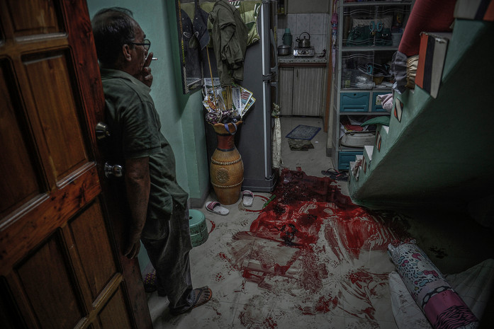 Marianito Libo-on smokes a cigarette as he stares at a pool of blood belonging to his son Jomar, who was shot numerous times by masked assailants in front of his wife and children, in Quezon city, Philippines, June 14, 2017.