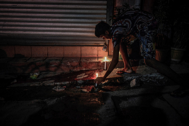 A resident lights candles next to a pool of blood belonging to a suspected drug user who was shot dead by unknown assailants in Navotas, Philippines, June 20, 2017.