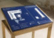 Das Foto stellt eine blaue Orientierungsstation mit ertastbarer Übersichtskarte dar. Die Station sieht aus wie ein Tisch, dessen blaue Tischplatte angekippt ist, dass alle den Inhalt gut erkennen und ertasten können. Das ist auch in sitzender Position möglich. Es ist eine sehr formschöne Orientierungsstation in einem französischen Museum. Folgende Informationsarten sind enthalten: Weiße Schriftzeichen, Brailleschrift, taktile Lagepläne zu den Laufwegen durch die Museumsanlage, die wichtigsten Exponate und Orientierungspunkte, ein Kompass sowie auf der rechten Hälfte des Orientierungstisches Detailangaben zu einem markanten Exponat einem sehr hohen Obelisken. Über einen Kopf können Hörtexte in verschiedenen Sprachen und Sprachausprägungen zugleich gehört werden. So können z.B. erblindete Menschen gleichzeitig den Plan ertasten und Informationen dazu anhören. Die Orientierungsstation ist eine runde Sache für alle Museumsbesucher, denn sie gibt jedem die relevanten Informationen aus.