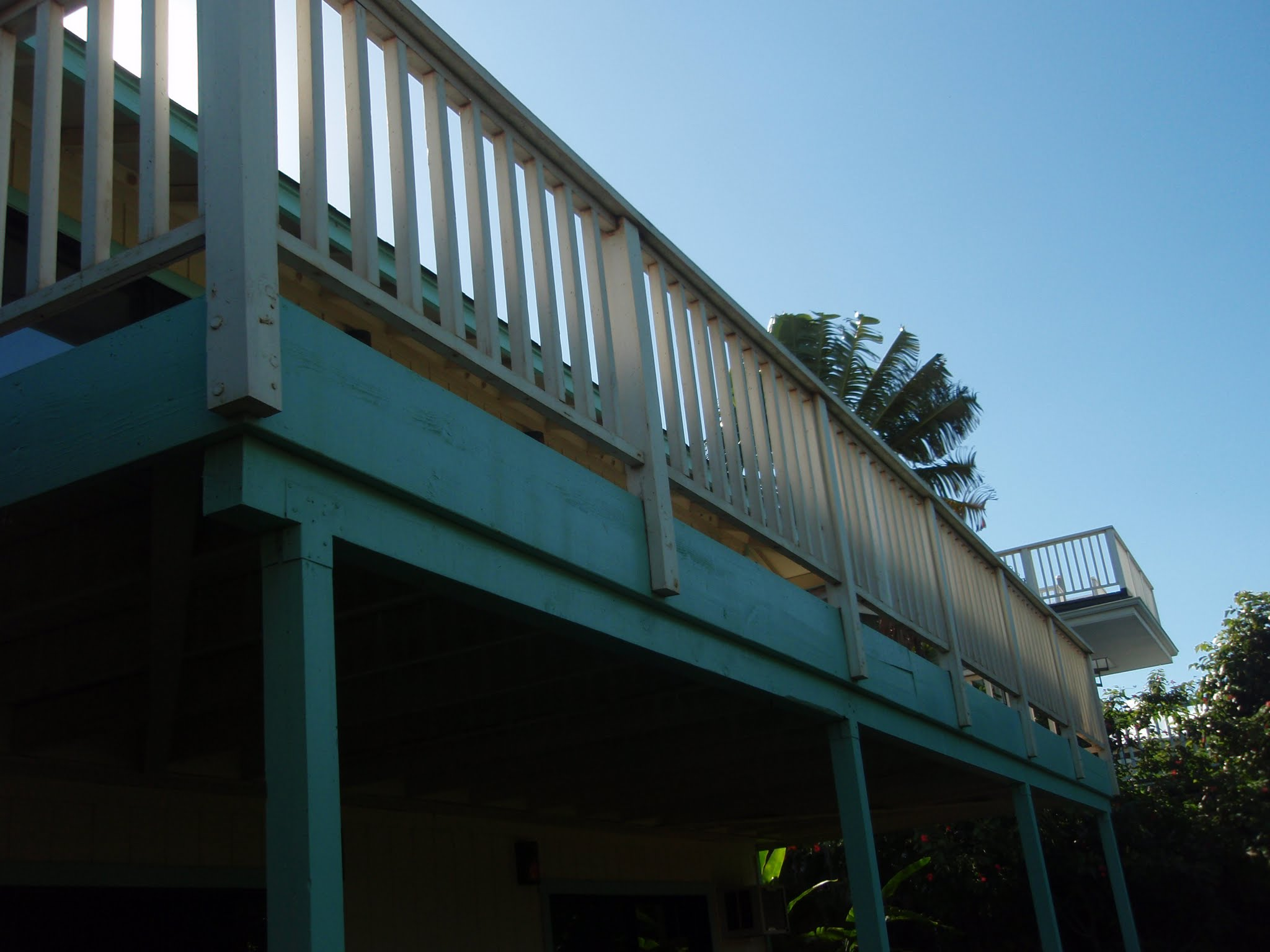 The old rear deck with wood posts & railing befroe restoration
